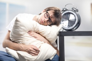 Sad man holding pillow and the clock